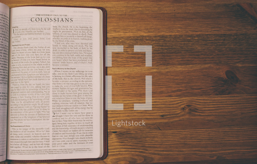 Bible on a wooden table open to the book of Colossians.