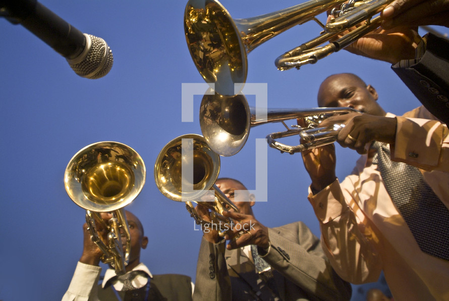 Microphone pointed to musicians playing brass instruments