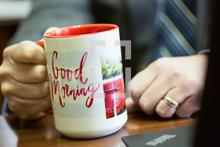 """Businessman starting his day with a coffee mug that says """"Good Morning""""."""