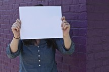a woman holding up a blank piece of white paper