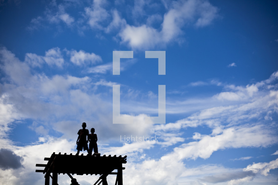 boys standing on a roof under white clouds in a blue sky