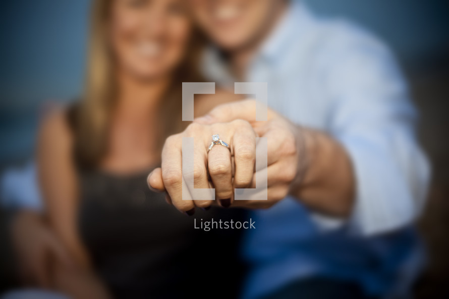 Couple showing engagement ring