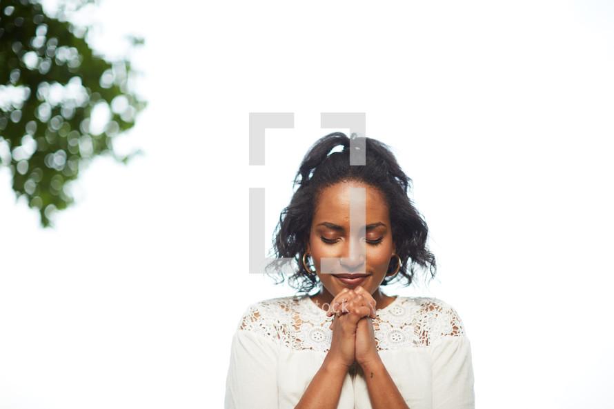 an African American woman praying outdoors