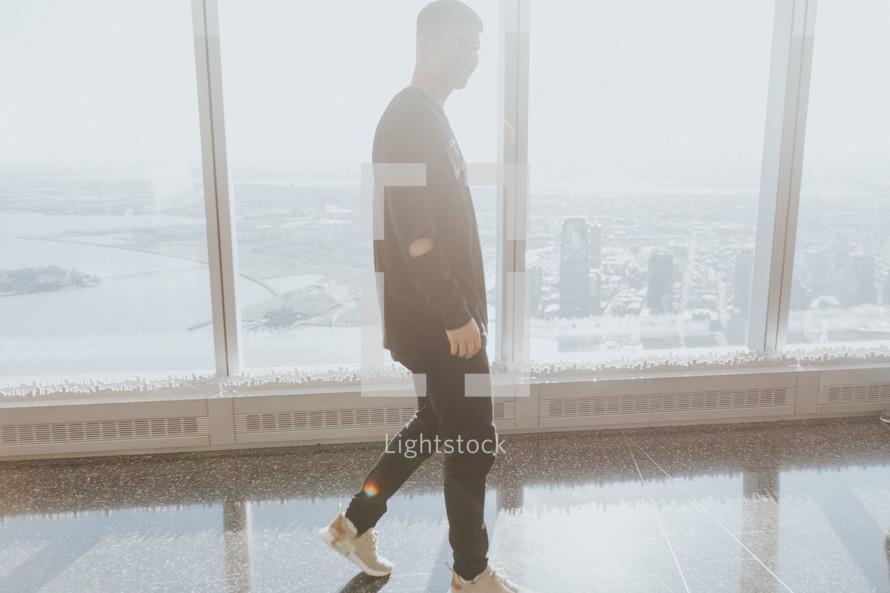 a man walking in front of windows in a skyscraper