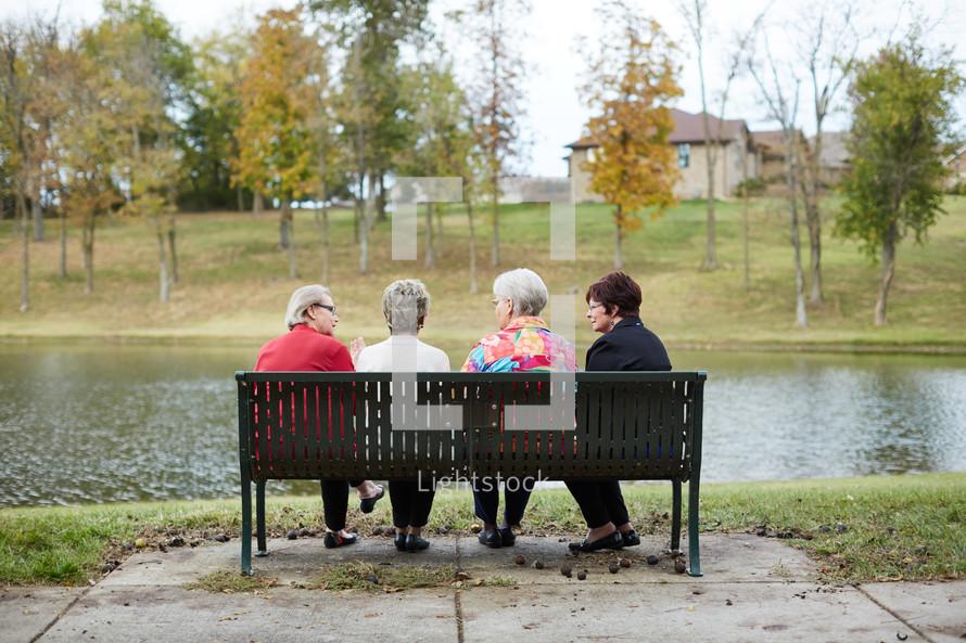 elderly women sitting on a park bench talking