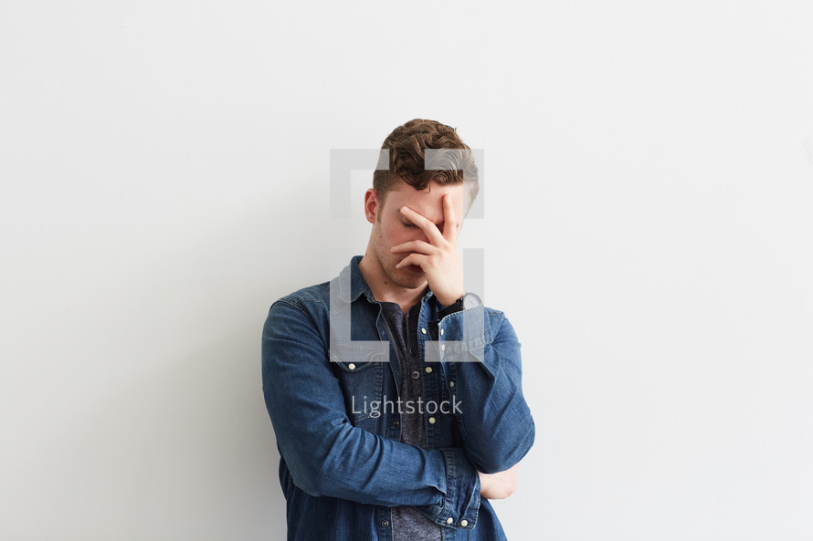 a man covering his face with his hand