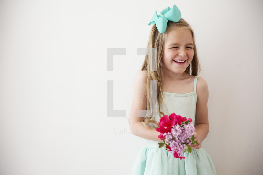 portrait of a giggling little girl holding flowers.