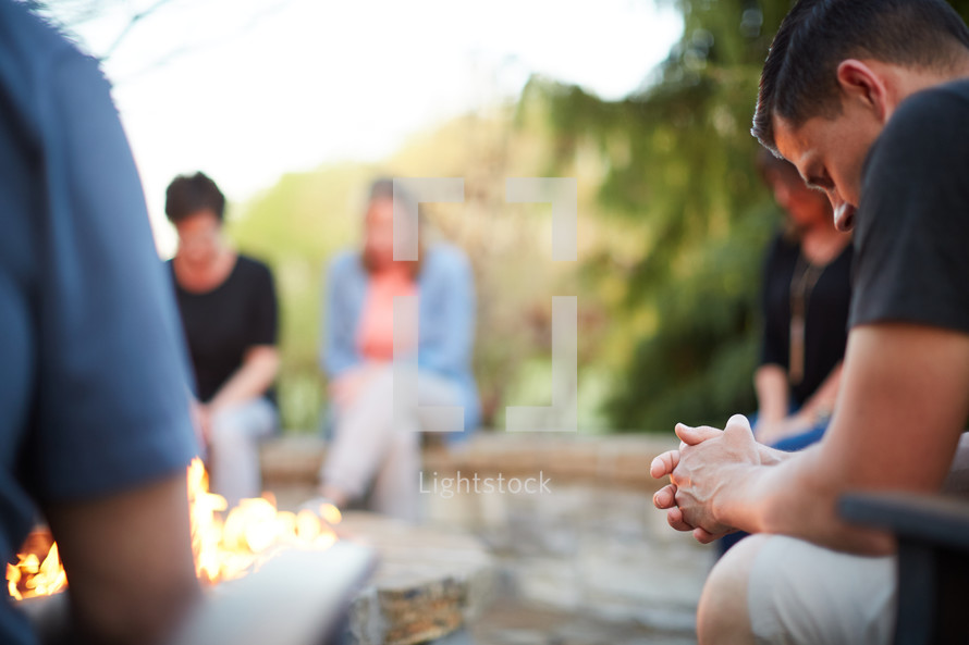 friends sitting around a fire pit praying