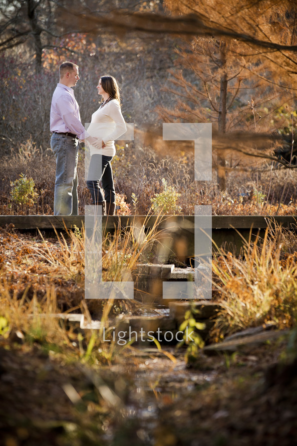 man with his hands on the belly of his pregnant wife standing on a small bridge on a nature trail