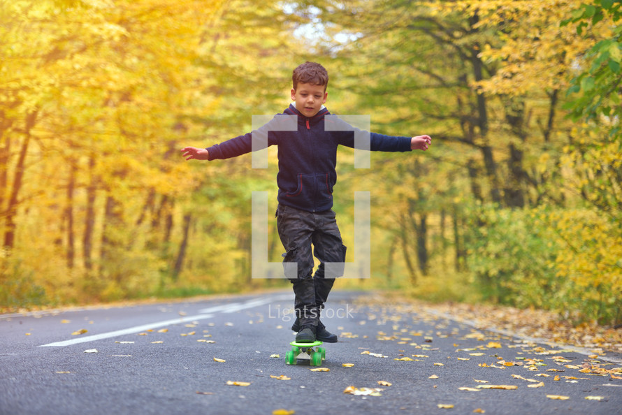 boy riding skateboard outdoors in autumn environment on sunset warm light