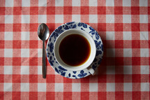 coffee cup and saucer on a red checkered tablecloth
