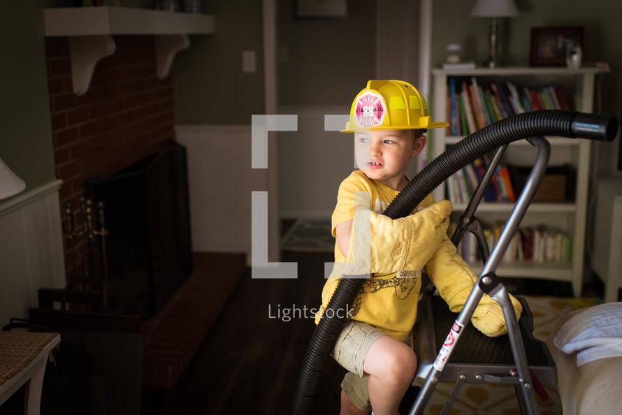 a boy pretending to be a firefighter