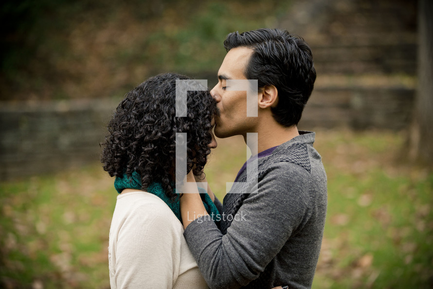 Man kissing woman on the head as they stand in a park.