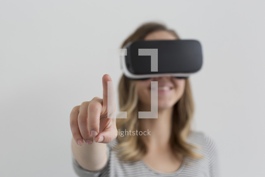 A woman wearing VR glasses and pointing