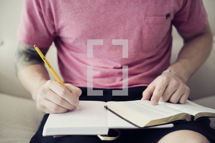 man writing in a journal and reading a Bible
