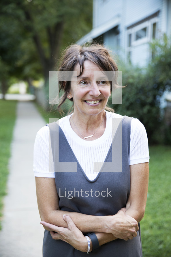 a woman standing outdoors on a sidewalk