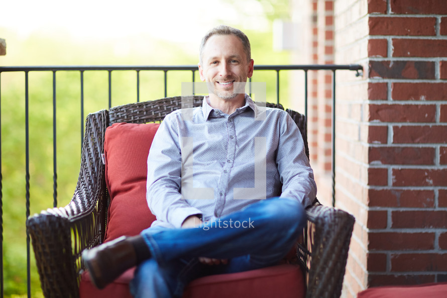 a man sitting on a porch relaxing