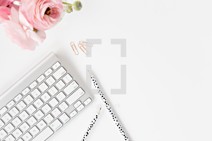 pink flowers, pencils, computer keyboard, and paperclips