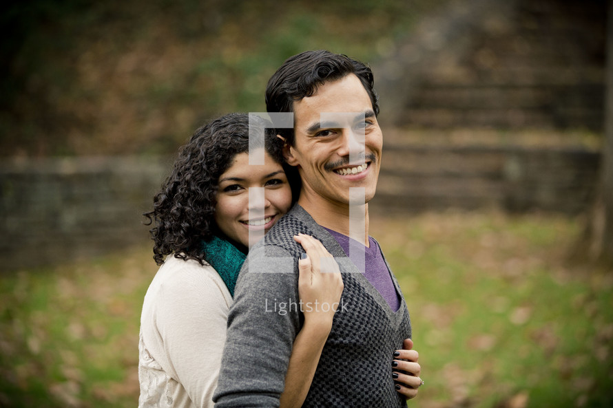Smiling woman embracing smiling man from behind in park.