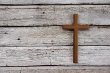 wooden cross on white wood boards