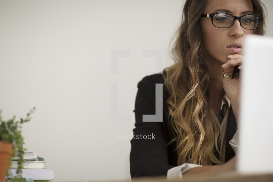a woman in the office working on a laptop