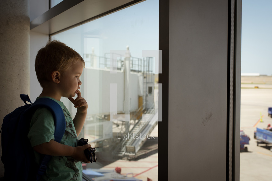 a child looking out a window at an airport