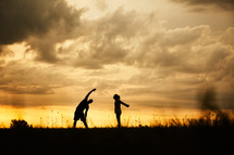 silhouettes of a couple stretching at sunset