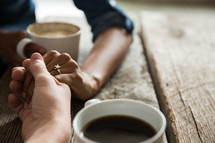 a couple holding hands and mugs