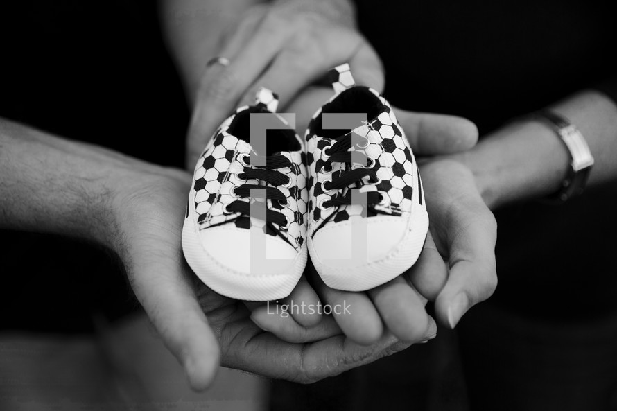open hands of a mother and father holding empty baby shoes