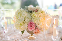 flowers in a vase as a centerpiece on a table at a wedding reception