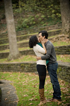 man and woman kissing outdoors