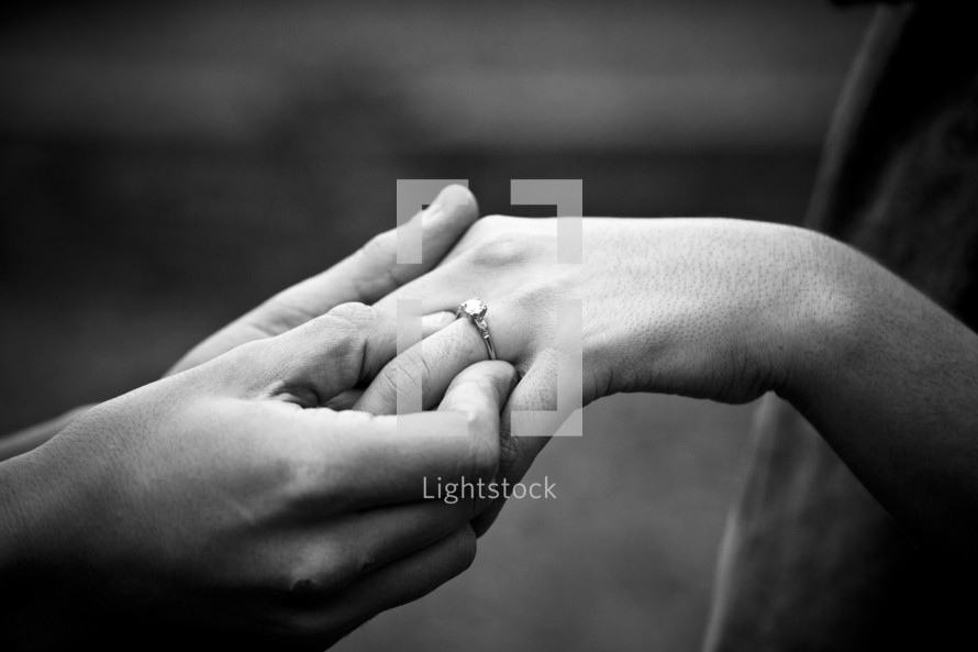 man slipping an engagement ring onto a woman's hand