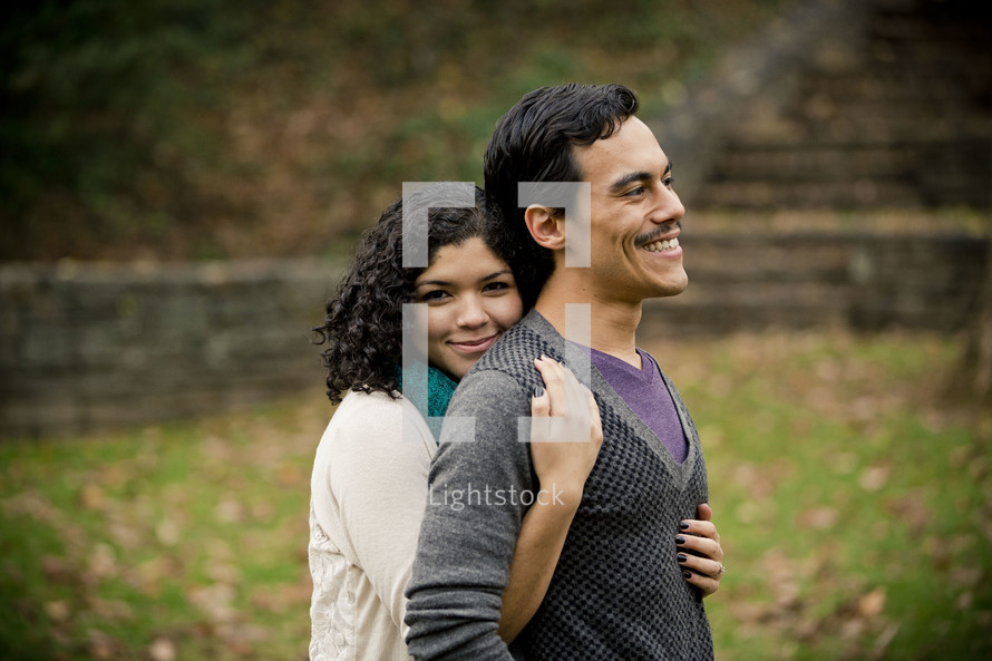 Woman embracing man from behind in park.