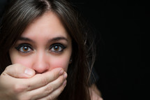 Speak no evil. A woman with her mouth and ear covered by a man's hands.