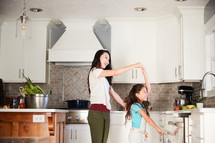 a mother and daughter dancing in a kitchen