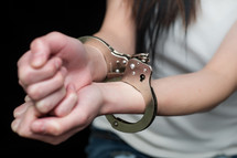Woman's wrists in handcuffs.