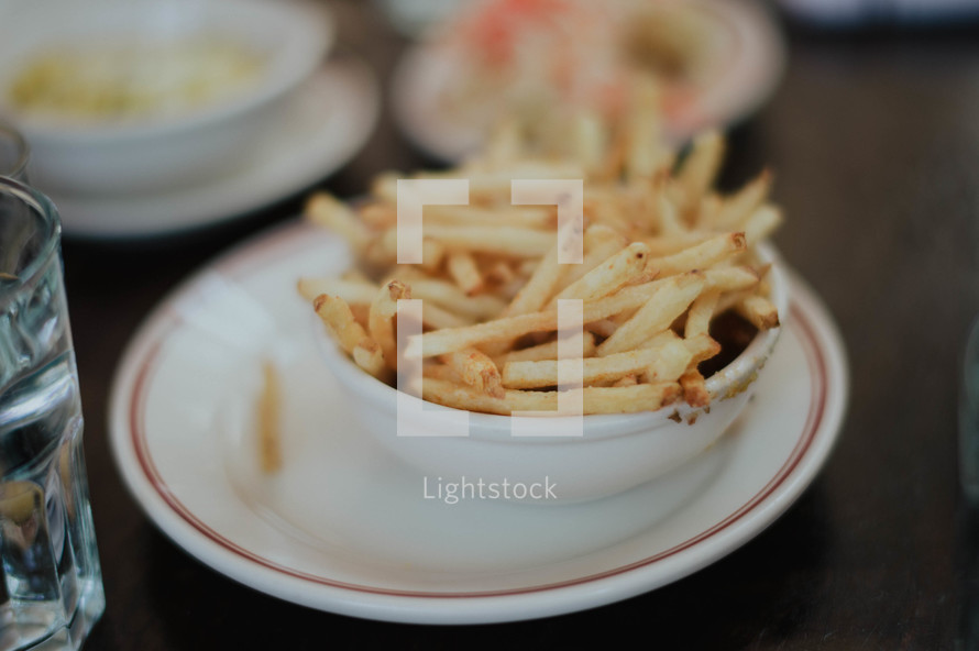 A bowl full of french fries on a dinner plate.