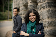Smiling woman in front of stone wall with smiling man looking at her in the background.