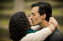 Man and woman kissing on the lips in the park.