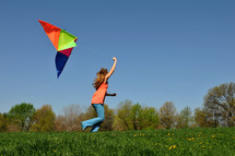 girl child running with a kite