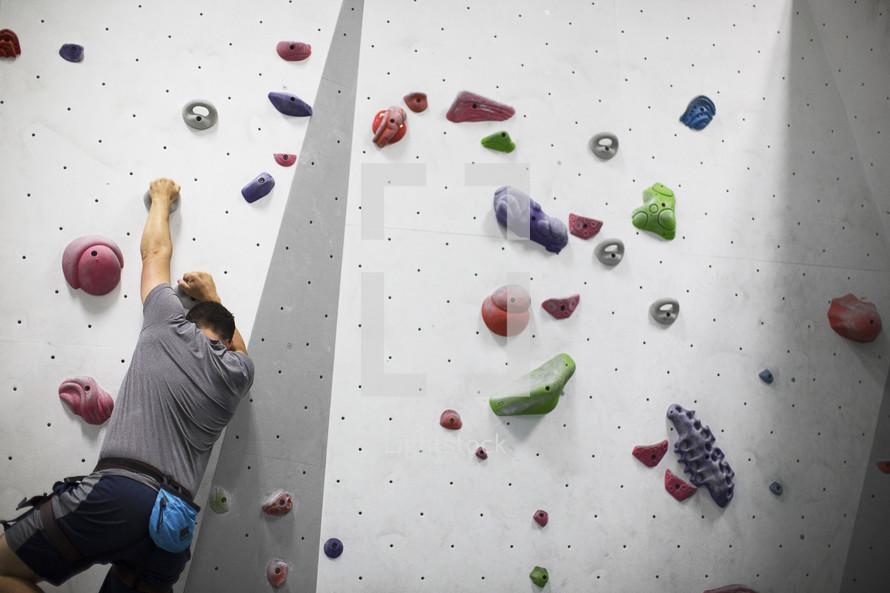 man climbing a rock wall.