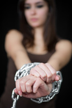A woman with chained hands.