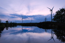 Wind turbines along a pond.