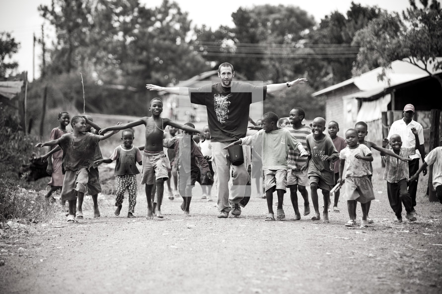 man followed by a group of children