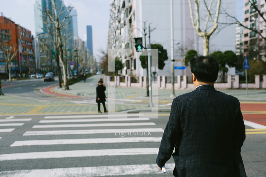 a man crossing a crosswalk in a city