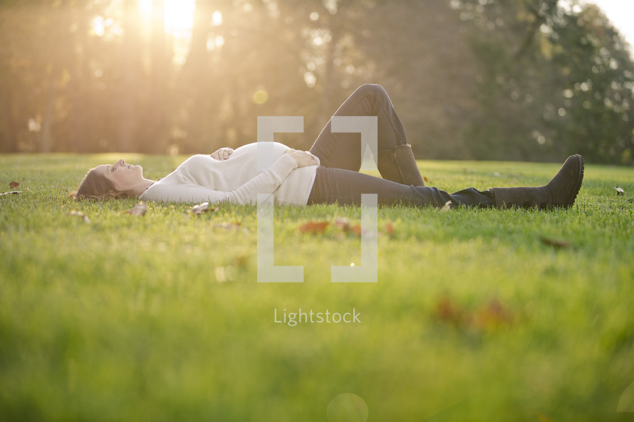 pregnant woman lying in the grass