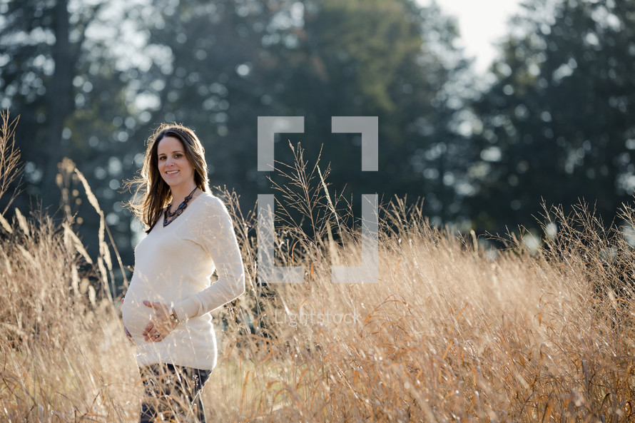 pregnant woman in a field holding her belly