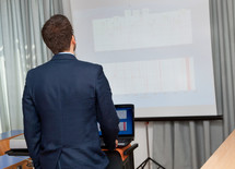Businessman shows a project with notebook and projector.