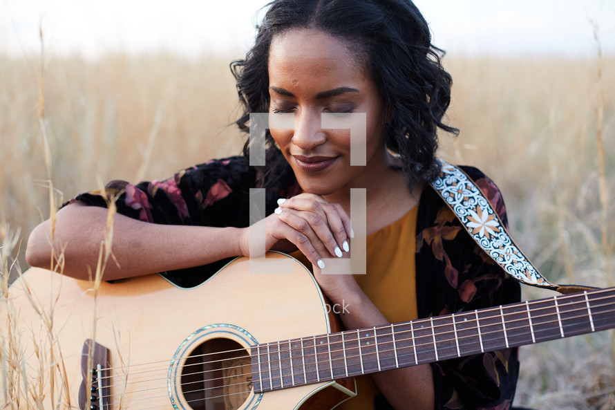 a woman sitting in a field with a guitar praying