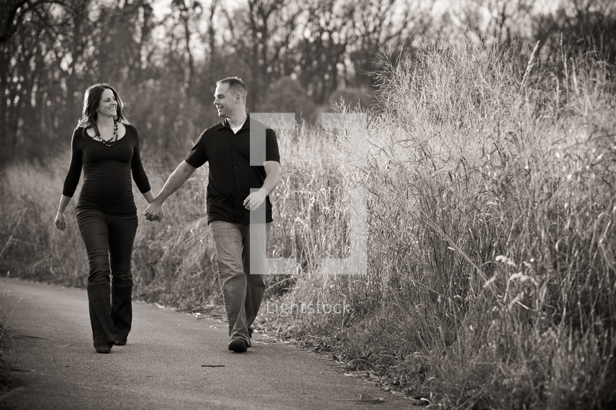 man and pregnant woman holding hands walking on a trail
